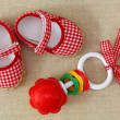 Baby rattle and red shoes — Stock Photo