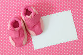 Pink baby shoes and blank note — Stock Photo