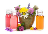 Mortar with fresh flowers and essential oil — Stock Photo