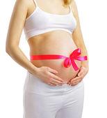 беременная женщина с розовой лентой на живот, изолированные на белом фоне — Стоковое фото