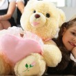 Little girl is hugging big teddy bear — Stock Photo