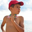 A boy in a baseball cap, standingagainst the backdrop of the sea — Stock Photo