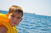 Boy in life jacket, standing in the background of the sea — Stock Photo