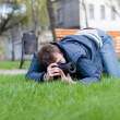 Photographer Takes a Shot on Green Grass - Stock Photo