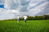 Happy Couple running on a grass — Stock Photo