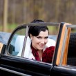 Beautiful bride in retro car — Stock Photo
