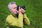 Photographer on green grass — Stock Photo
