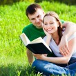 Couple sitting in park reading book - Stock Photo