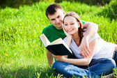Couple sitting in park reading book — Stockfoto