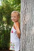 Beautiful girl standing beside a tree — Stock Photo