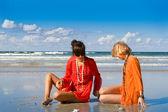 Two beautiful women sitting on beach — Stock Photo