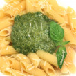 Delicious italian pasta with pesto sauce and basil leaves - Stock Photo