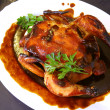 Roast chicken on a white plate with brown sauce — Stock Photo