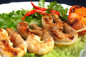 Grilled prawns on bamboo sticks served on lettuce — Stock Photo
