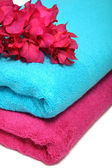 Pink and blue towels with flowers on a table — Zdjęcie stockowe