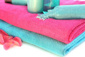 Pink and blue towels with shampoo, solt, cream, body lotion, bat — Stock Photo