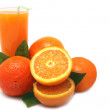 Oranges with green leaves and glass of juice on a white backgrou — Stock Photo