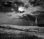 Dramatic and moody black and white image of a church on a hill being lit by — Stock Photo