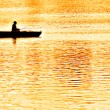 An angler fishing from a punt in the evening glow — Stock Photo