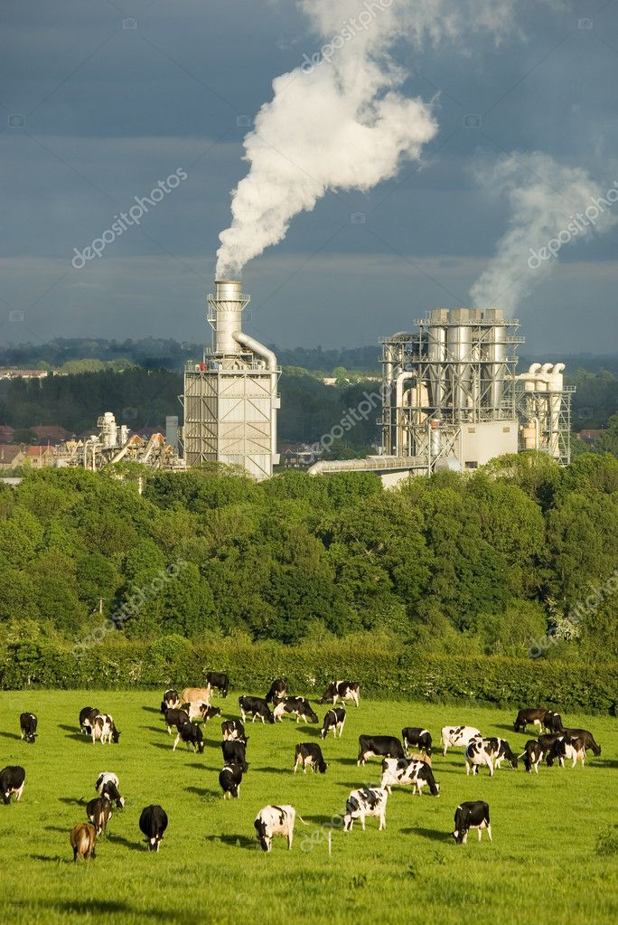 A factory belching smoke with farmland in the foreground.   #5497032