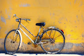 Old bike against the wall at home — Stock Photo