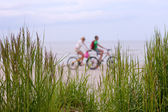 Couple on a bike ride along the beach — Stock Photo