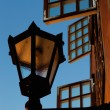 Lantern on the wall in the background of open windows - Stock Photo