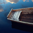 Wooden boat in the clouds reflected in water - Stock Photo