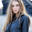 A beautiful young girl with hair fluttering in the wind in jacket — Stock Photo