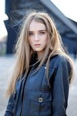 美丽的年轻女孩在夹克在风中飘扬的头发 — 图库照片