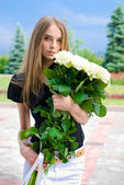 Girl holding a huge bouquet of roses — Stock Photo