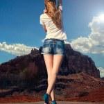 meisje wandelen langs de weg in de woestijn — Stockfoto