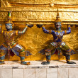 Golden guards are holding the chedi - Stock Photo