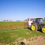 traktor na poli prská škůdců ochrana — Stock fotografie