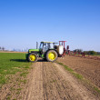 Stockfoto: Tractor on field sputtering pest protection