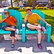 Two brothers are sitting on a art deco park bench in south Miami — Stock Photo #5526352