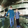 Young boys on a moving staircase inside the airport — Stock Photo