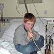 Young boy in hospital using a machine — Stock Photo #5526781