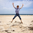 Boy enjoys the beautiful beach and jumps — Stock Photo