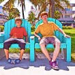Two brothers are sitting on a art deco park bench in south Miami — Stock Photo #5528189