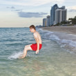 Boy jumps with speed into the ocean - Stock Photo