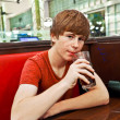 Attractive boy sitting in a diners at night — Stock Photo