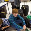 Boys is sitting on thr baggage waiting for check in at the airport - Stock Photo