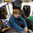 Boys is sitting on thr baggage waiting for check in at the airport — Stock Photo