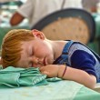 Boy falling asleep on the dinner table - Stock Photo