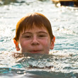 Boy with red hair is swimming in the pool and enyoing the fresh - Lizenzfreies Foto