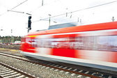 Red train in motion in the station — Stock Photo