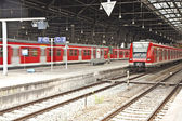 Iron classicistic train station from inside with red trains — Stock Photo