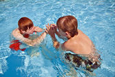 Brothers have fun in the outdoor pool — Stock Photo