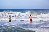 Brothers having fun in the waves of the ocean — Stock Photo